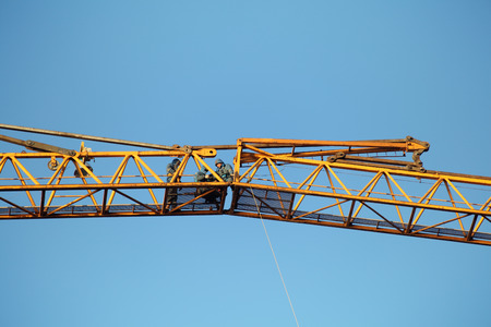 jib: St. Petersburg, Russia - October 30, 2014: Workers installers are working at high altitude, fixing sections of the working jib construction tower crane. Editorial