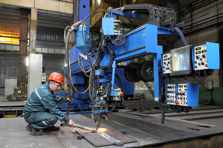 St. Petersburg, Russia - October 10, 2014: Industrial processing metal, automated submerged arc welding process. Work controls the setting for butt welding of steel sheets, metal working machine.