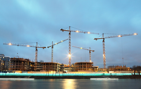 extramural: Construction site of a residential building, tower cranes with evening lights mast and jib.