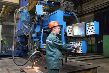 welding machine: St. Petersburg, Russia - October 10, 2014:Automatic submerged arc welding, the working operator controls the welding robot, standing at the control panel. Butt welding machine for steel sheets. Editorial