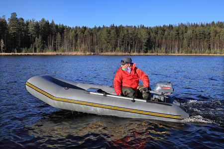 outboard: Leningrad Region, Russia - October 20, 2013: One unidentified man in a red cloak, manages gray inflatable rubber boat with an outboard motor on a blue forest lake in the fall on a sunny day. Editorial