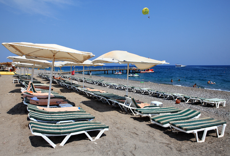 pebble beach: Kemer, Turkey - August 29,  2014:  Sun loungers and parasols on a pebble beach in the resort area of Antalya coast.