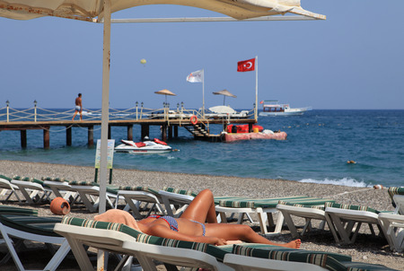 pebble beach: Antalya, Kemer, Turkey - August 29, 2014: Pebble beach near the village of Camyuva, sunbeds and umbrellas for holidaymakers at the resort tourists sunbathing girl lying on a sun lounger.