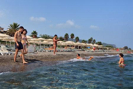 Kemer, Antalya, Turkije - 29 augustus 2014: Dorp Camuva, mediterrane badplaats, Toeristen zwemmen in het zeewater op eigen kiezelstrand met parasols en ligbedden, jong paar wandelingen in het water.