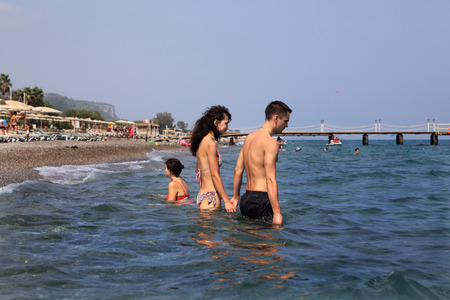 vacationing: Kemer, Antalya, Turkey - August 29, 2014: Village Camuva, Mediterranean resort, Couple goes deep into the sea, holding hands, tourists vacationing in the Turkish resort, swimming in the sea.
