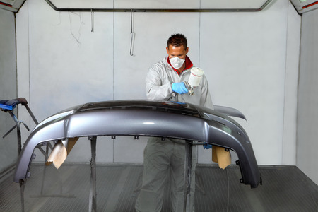Saint Petersburg, Russia - June 26, 2014: Painting bumper car spray booth auto repair shop, working in a protective mask and clothing, operates a spray gun. 報道画像