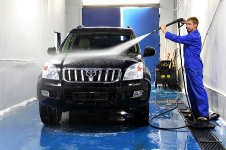 Saint Petersburg, Russia - June 26, 2014: Car maintenance,  manual car washing, Worker at Car Wash Shop,  Using Pressure Washers on Cars,  man washing car with compression water.