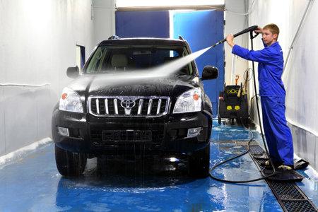 autolavaggio: San Pietroburgo, Russia - 26 giugno 2014: la manutenzione dell'automobile, lavaggio auto manuale, Operaio al Car Wash negozio, con rondelle di pressione sulle auto, lavaggio auto dell'uomo con l'acqua di compressione.