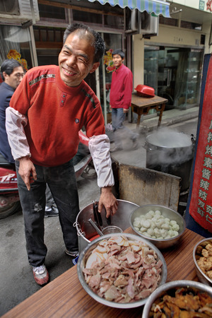 affable: Shanghai, China - April 20, 2010: Outdoor affable chef prepares dishes trades in a narrow street.