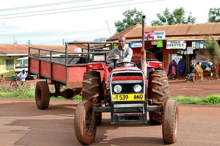 red truck: Makuyuni, Arusha, Tanzania - February 13, 2008: African, Tanzanian farmer tractor driver, sitting behind the wheel of a agrimotor without a cab, with bodywork trailer.