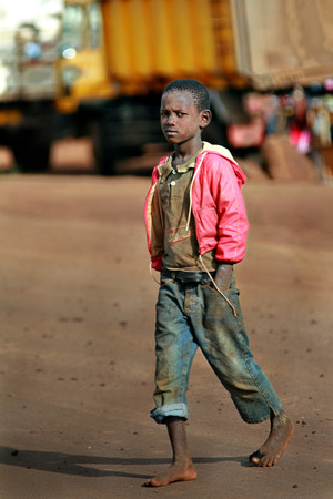 muddy clothes: Makuyuni, Arusha, Tanzania - February 13, 2008: Unknown African barefoot black gamin boy in pink jacket, about 10 years old, walking barefoot, hands in pockets, jeans rolled up.