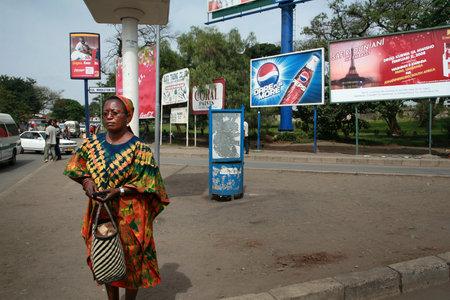 publicidad exterior: Arusha, Tanzania - 10 de febrero 2008: Desconocido piel oscura mujer adulta Africana de pie en un parche de polvo cerca de la carretera, rodeado de la publicidad exterior en vallas publicitarias.