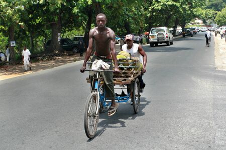 city bike: Dar es Salaam, Tanzania - February 21, 2008: African man traveling on the highway on a tricycle, a huge trunk of a bicycle lying fruit.