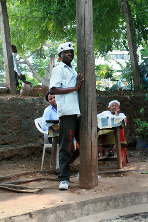 es: Dar es Salaam, Tanzania - February 21, 2008: Unknown black teenager in a white shirt standing at the side of the road.