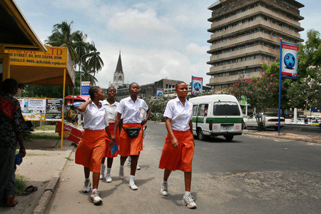hebraism: Dar es Salaam, Tanzania - February 21, 2008: Four black African girl in uniform go along edge of the carriageway of the road. Editorial