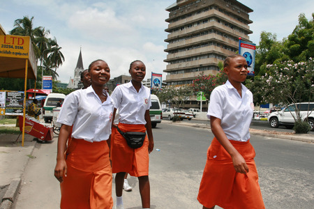 es: Dar es Salaam, Tanzania - February 21, 2008: Four black african girl in orange skirts and white blouses.