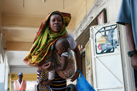 es: Dar es Salaam, Tanzania - February 21, 2008: Black African woman with an infant in a sling. Editorial