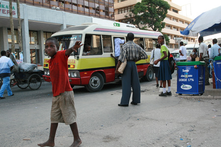 10 years old: Dar es Salaam, Tanzania - February 21, 2008: Unidentified boy, about 10 years old, walks past a crowded public bus.