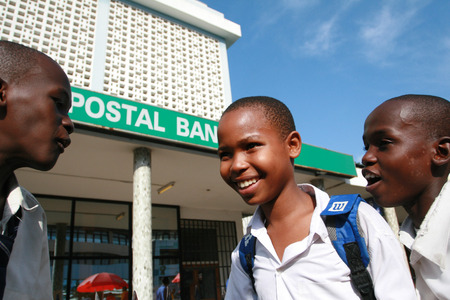 neighborly: Dar es Salaam, Tanzania - February 21, 2008: Three black African boys older students, chatting in the street, in the city center.