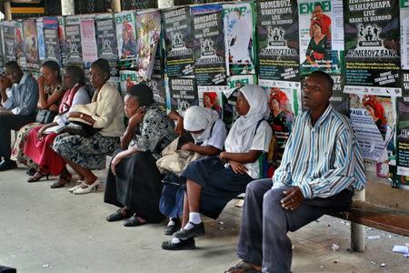 show bill: Dar es Salaam, Tanzania - el 21 de febrero de 2008: La estaci�n de autobuses lanzadera, los lugare�os se sientan en un banco p�blico, huyendo del sol a la sombra, sobre un fondo de vallas publicitarias. Editorial