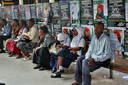 fleeing: Dar es Salaam, Tanzania - February 21, 2008: The shuttle bus station, locals sit on a public bench, fleeing from the sun in the shade, on a background of billboard posters.