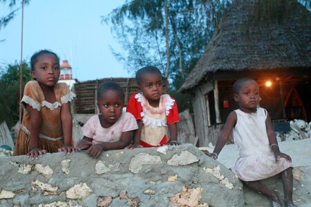 Zanzibar, Tanzania - February 19, 2008: Four unidentified small black African Arabian girl, the approximate age of 4-6 years, resting on a stone fence in the evening, after sunset. Editorial