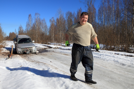motorcar: Nazia village, Leningrad Region, Russia - March 17, 2015: Vehicle stuck on ice road in forest, front wheel fell into a hole, the driver uses a winch to rescue the car.