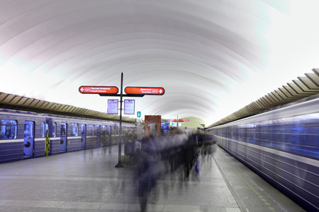filed: St. Petersburg; Russia - March 7; 2014: Located deep underground, subway station Polytechnique, flows of passengers move through the platform, the train with blue wagons filed for planting. Editorial