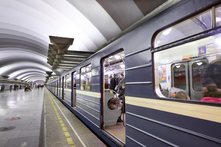 St. Petersburg, Russia - March 7,  2014: Passenger platform at a subway station, train with blue wagons standing with open doors. Deep underground station Ploshchad muzhestva. 新聞圖片
