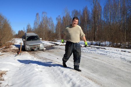 motorcar: Nazia village, Leningrad Region, Russia - March 17, 2015: Car stuck on a forest road, front wheel fell into ravine in the ice, the man pulls the cable car winch.