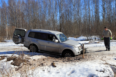 car hoist: Nazia village, Leningrad Region, Russia - March 17, 2015: Vehicle is stuck in a hole in the winter forest road, the driver install a winch to rescue the car. Editorial