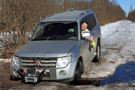 roadless: Nazia village, Leningrad Region, Russia - March 17, 2015: Motorist sitting behind the wheel of a car that was stuck in the creek on the ice road in woods, in his hand he holds a remote control winch. Editorial