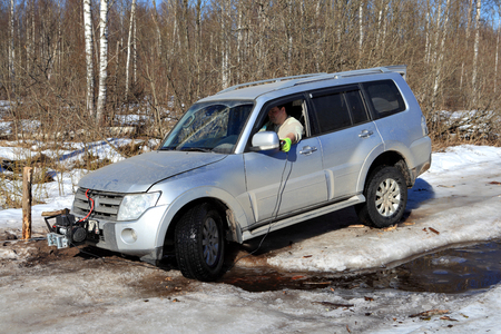 roadless: Nazia village, Leningrad Region, Russia - March 17, 2015: Vehicle is stuck in the forest creek in an ice wood road, the driver uses a winch with remote control to pull the car out of the pit.