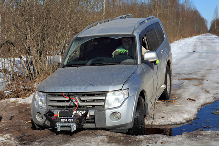 roadless: Nazia, Leningrad Region, Russia - March 17, 2015: The driver controls the winch while sitting in  passenger compartment of  car, passenger car wheels fell into  pit road, on  road spring melts  ice.