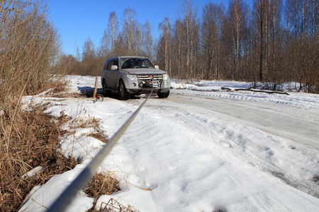 Nazia village, Leningrad Region, Russia - March 17, 2015: Salvation vehicle which has got stuck on a forest road, using the winch with a long cable.