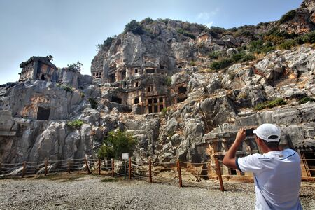 take a history: Myra, Antalya, Turkey - August 28, 2014: Tourist take photos Ancient lycian Myra rock tombs ruins at Turkey Demre.