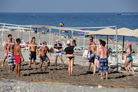 Camyuva village, Kemer, Turkey - August 25, 2014: Men and women playing beach volleyball on the private beach resort.