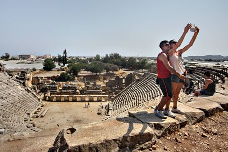 take a history: Myra, Antalya, Turkey - August 28, 2014: Myra, Antalya, Turkey - August 28, 2014: Ancient amphitheater, couple take a picture together while visiting a tourist attraction, smiling and having fun.