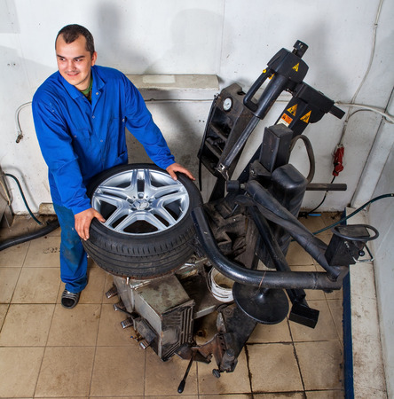 tire fitting: Saint Petersburg, Russia - June 26, 2014: Car wheel tyre fitting or replacement, Car Service Station, Automatic Car Tyre Changer, tire mounting machine.