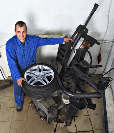 tire fitting: Saint Petersburg, Russia - June 26, 2014: Auto repairman loading automobile car wheel at tyre fitting machine during tire replacing.