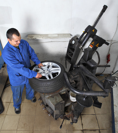 tire fitting: Saint Petersburg, Russia - June 26, 2014: Station maintenance, repair car wheels, tyre changing machine, mechanic fixing tire in car service.