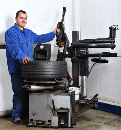 tire fitting: Saint Petersburg, Russia - June 26, 2014: Workstation, maintenance vehicles, Worker operates the machine automatic tire mounting. Editorial