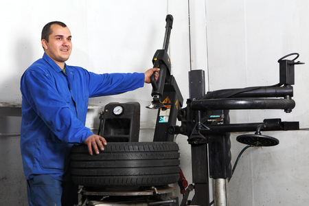 tire fitting: Saint Petersburg, Russia - June 26, 2014: Tire mounting equipment,  auto mechanic repairs a car wheel, Service Station.