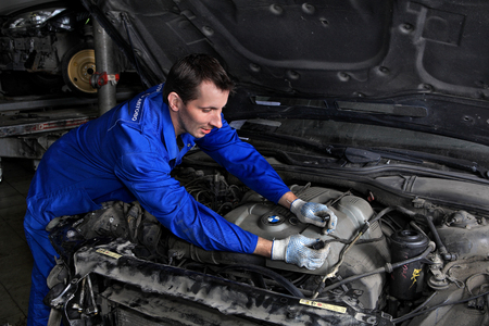 electrical system: Saint Petersburg, Russia - June 26, 2014: Saint Petersburg, Russia - June 26, 2014: Service station workers opened the hood and check the  car electrical system, repair car service workshop.