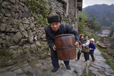 agriculturalist: Langde Village, Guizhou, China - April 16, 2010: Elderly Asian man climbs the stone mountain road in the countryside of China, holding a wooden barrel.
