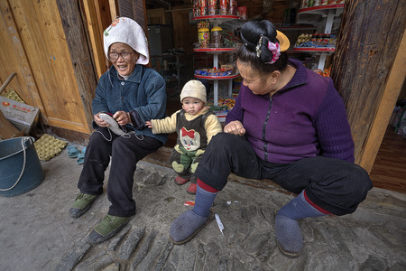 threshold: Langde Village, Guizhou, China - April 16, 2010: Two rural Chinese woman sitting on the threshold of the village shop, next to a year-old baby. Editorial