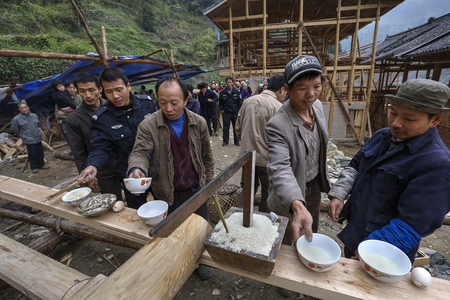 villagers: Langde Village, Guizhou, China - April 16, 2010: Peasants, farmers, villagers mountain village celebrate Start of construction of the farmhouse, men drink alcohol, eat rice, fish and eggs. Editorial