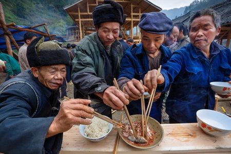 Langde Village, Guizhou, China - 16. April 2010: feierlichen Zeremonie der Baubeginn des neuen Bauer Bauernhaus, Gäste ländliche Ferien zusammen essen Fisch und Reis mit Stäbchen, Dorf Miao Editorial