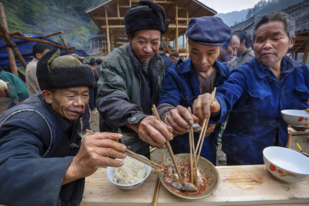 Langde Village, Guizhou, China - April 16, 2010: Festive ceremony of the start of construction of new peasant farmhouse, guests rural holiday together eat fish and rice using chopsticks, Miao village Editorial
