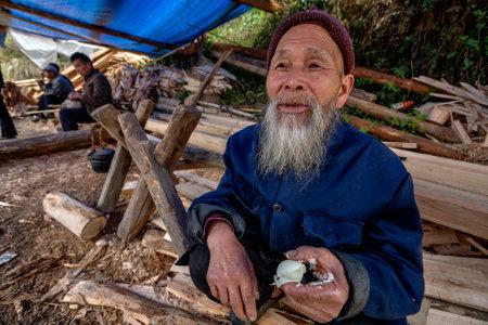 village man: Langde Village, Guizhou, China - April 16, 2010: Langde Shang ethnic minority Miao Village, elderly asian man eating boiled chicken egg.